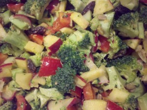 A salad made from broccoli, apples, raisins, sunflower seeds, sweet red pepper, radishes, dressed with olive oil, turmeric, garlic, lemon juice features Mediterranean flavors!